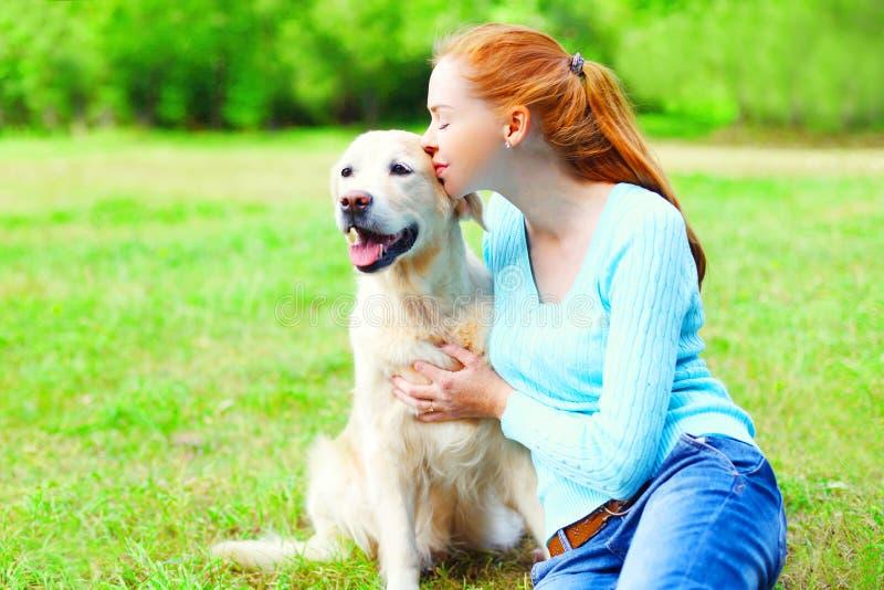Ögonblick av lycka! Den lyckliga ägarekvinnan kramar kyssgolden retrieverhunden på gräs arkivbild