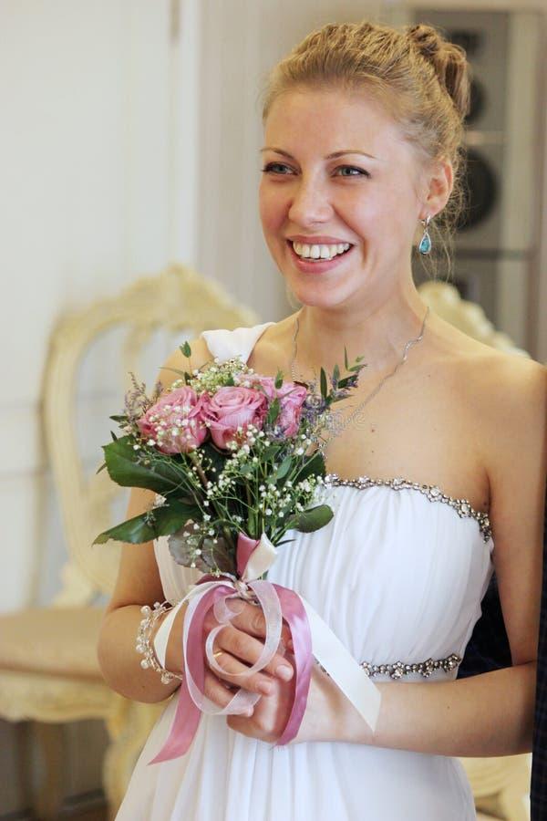 Ögonblick för förbindelsebröllopdag Över vit Bruden rymmer en härlig bröllopsklänning royaltyfri foto