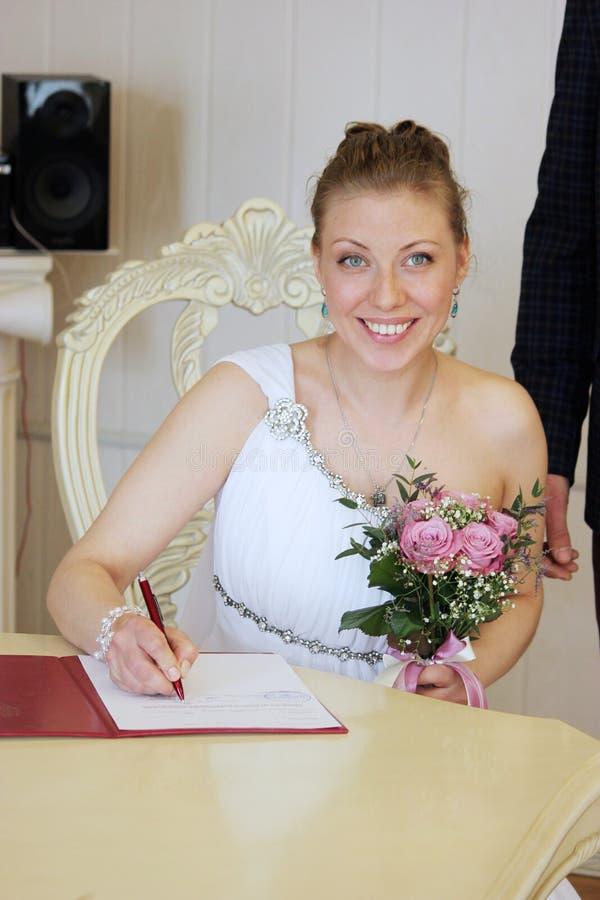 Ögonblick för förbindelsebröllopdag Över vit Bruden rymmer en härlig bröllopsklänning arkivbilder