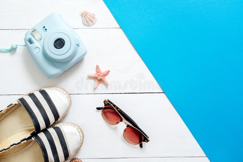 Ögonblicklig kamera, randiga sandaler, tappningexponeringsglas, snäckskal och sjöstjärna på vit träbakgrund Tillbehör och kläder  arkivbild