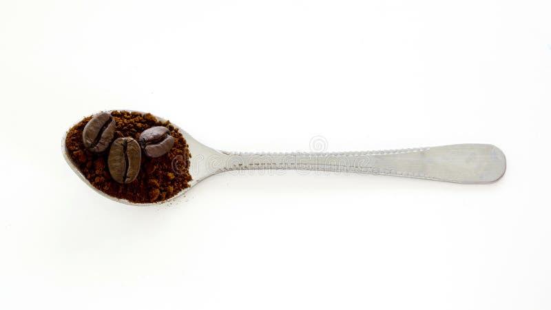 Ögonblickligt kaffe med stekkaffebönan i skeden arkivbild