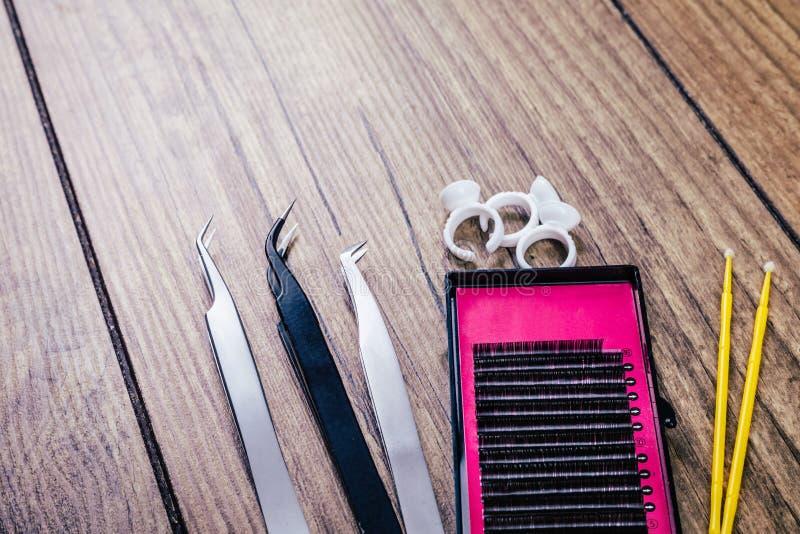 Ögonfransförlängningshjälpmedel på träbakgrund Tillbehör för ögonfransförlängningar Konstgjorda snärtar Top beskådar royaltyfria bilder