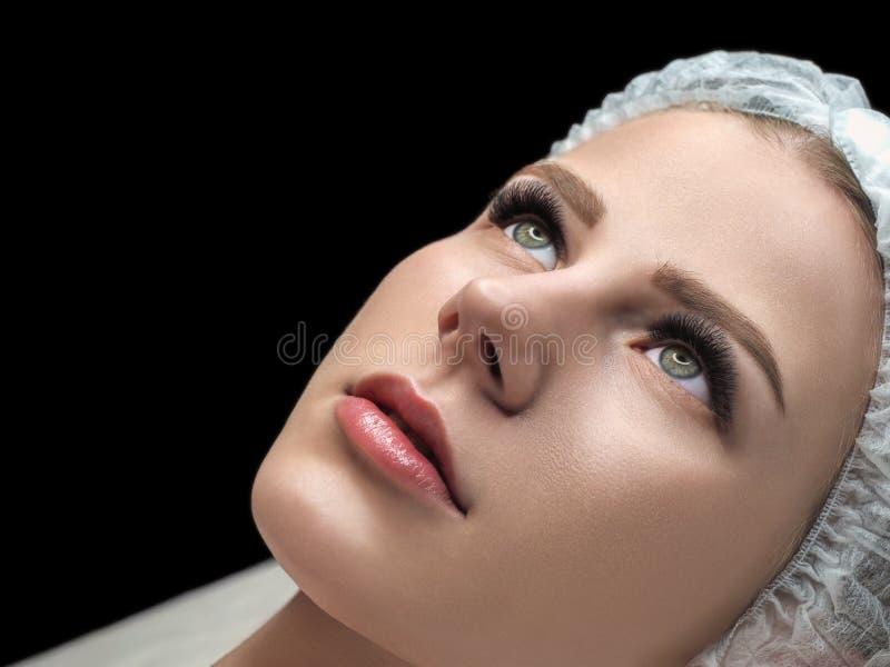 Ögonfransförlängningsresultat Kvinnlig framsida med långa svarta snärtar och disponibelt lock på soffan i skönhetsalongen som väl royaltyfri bild