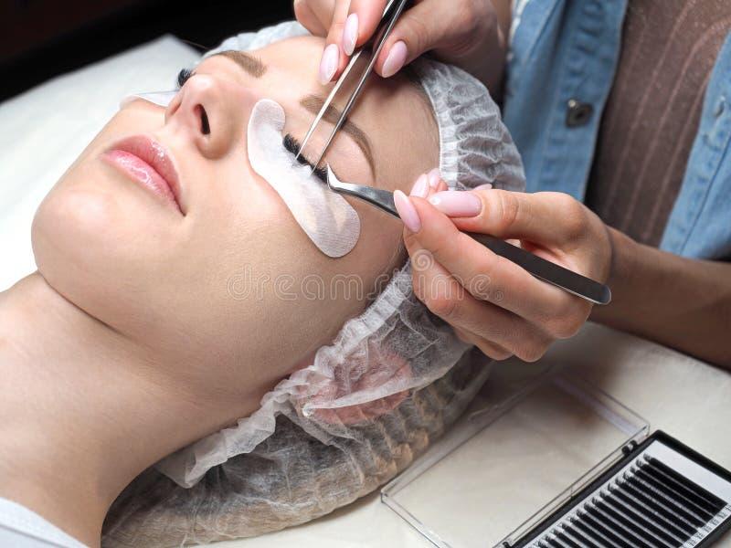 Ögonfransförlängningstillvägagångssätt Kvinnaframsida och expertfingrar med pincett, slut upp, selektiv fokus royaltyfri bild