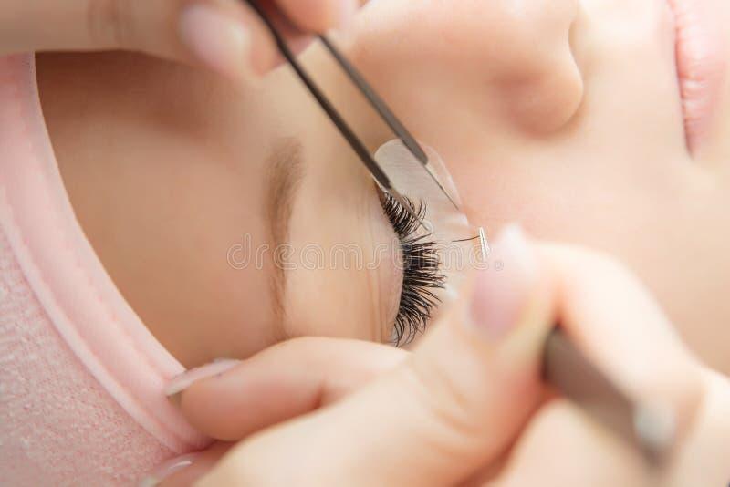 Ögonfransförlängningstillvägagångssätt Kvinnan synar med långa ögonfranser royaltyfri bild