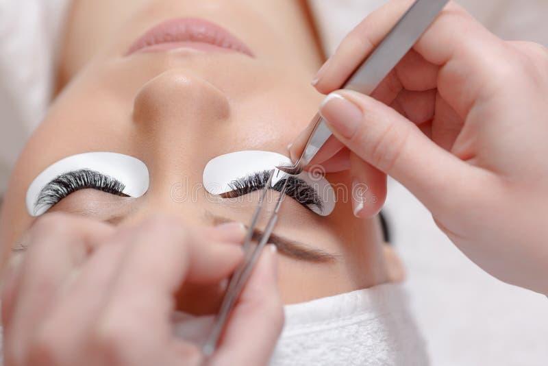 Ögonfransförlängningstillvägagångssätt Kvinnan synar med långa ögonfranser arkivbilder