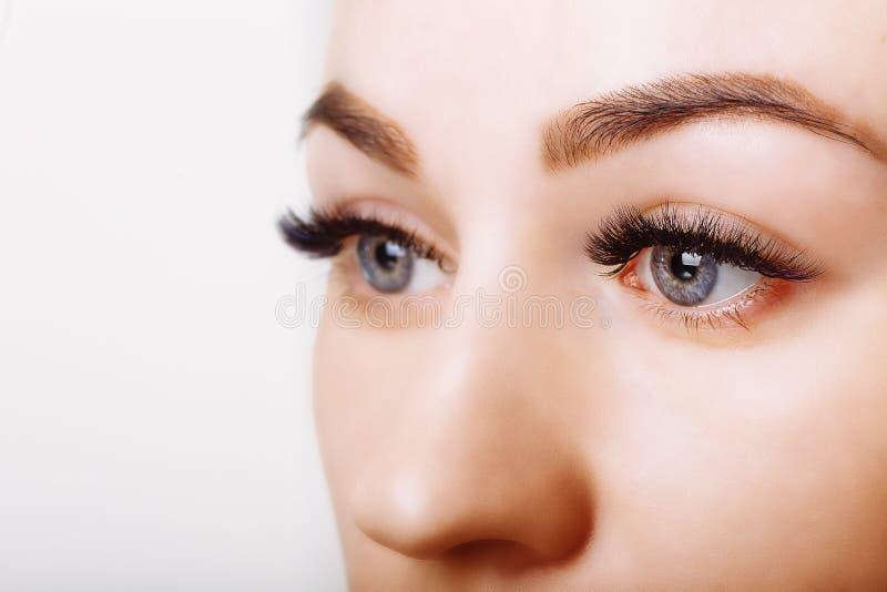 Ögonfransförlängningstillvägagångssätt Kvinnan synar med långa ögonfranser Nära övre, selektivt fokuserar fotografering för bildbyråer