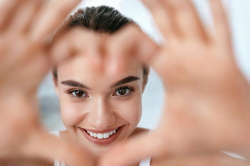 Ögonhälsa Härlig kvinnaframsida med hjärta formade händer _ arkivfoton