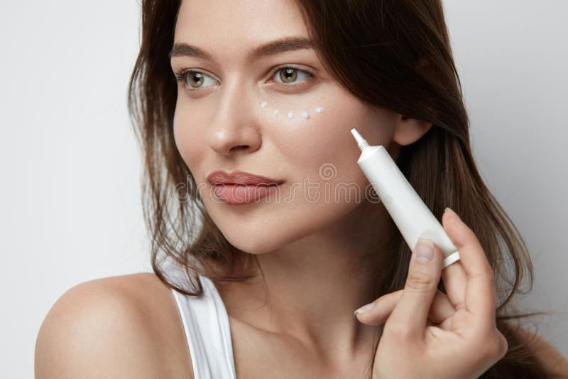 Ögonhudomsorg Härlig kvinna som applicerar ögonkräm arkivfoto