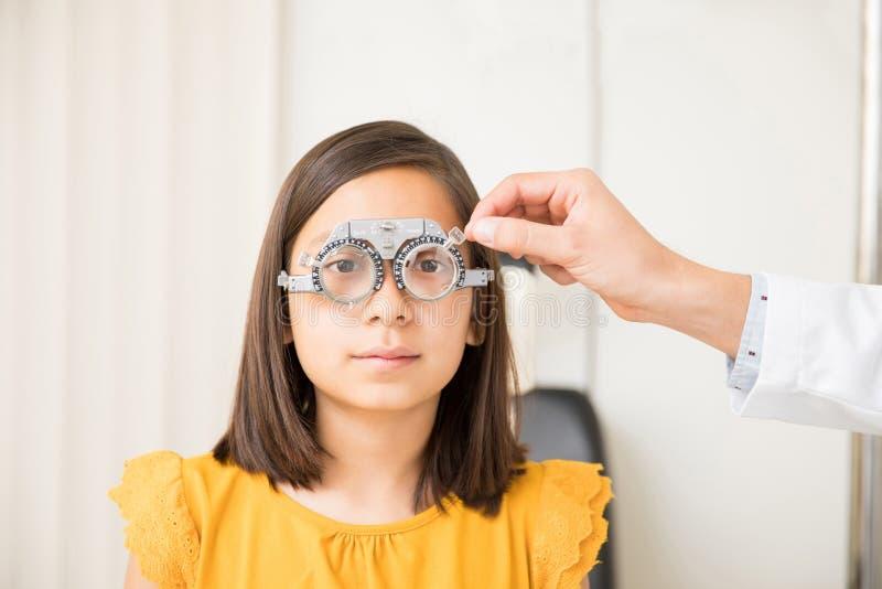 Ögonläkare och liten flicka med försökramen i klinik arkivbild
