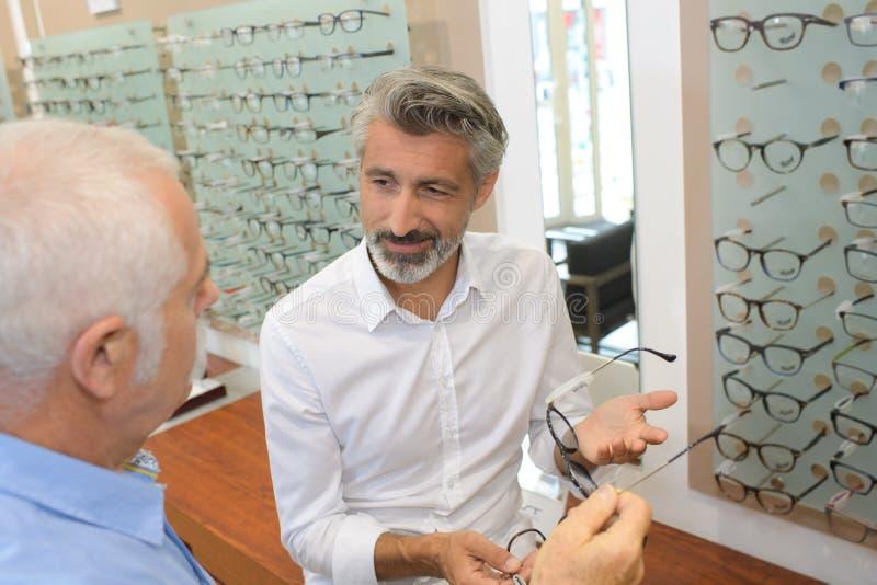 Ögonläkare- och manpensionär som väljer exponeringsglas på optiklagret arkivfoto