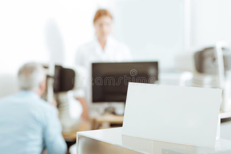 Ögonläkareanseende nära bärbara datorn, medan undersöka patienten royaltyfria foton