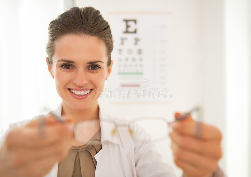 Ögonläkaredoktorskvinna som ger glasögon royaltyfri foto