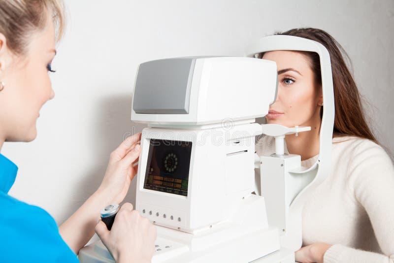 Ögonläkaren kontrollerar vision till hennes patient royaltyfri bild