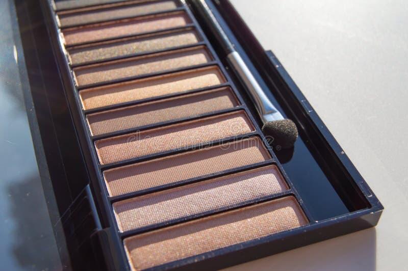 Ögonskugga i en palett av bruna och näcka skuggor med en makeupborste royaltyfri bild