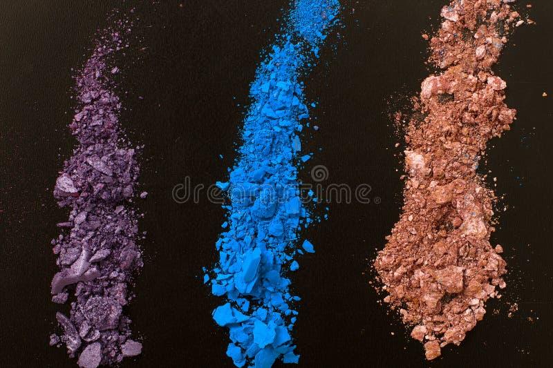 Ögonskuggor på svart bakgrund Krossad skönhetsmedel Sminkskönhetsmedel Bästa sikt och åtlöje upp royaltyfri foto