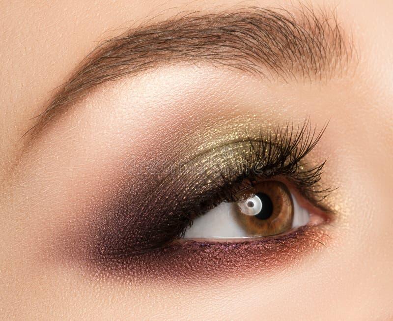 Ögonsmink med ljus modeguld--brunt ögonskugga royaltyfria foton