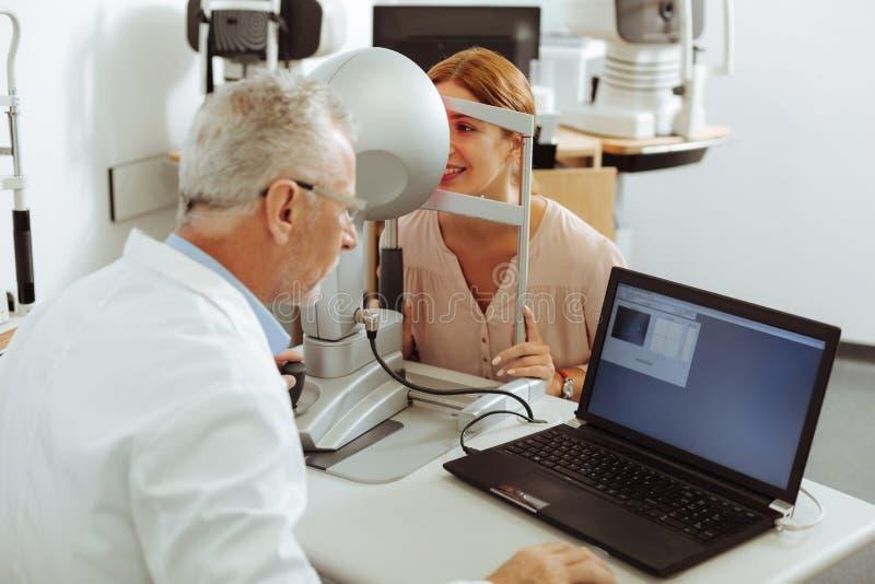 Ögonspecialist som använder bärbara datorn, medan undersöka ögonsikt royaltyfria foton