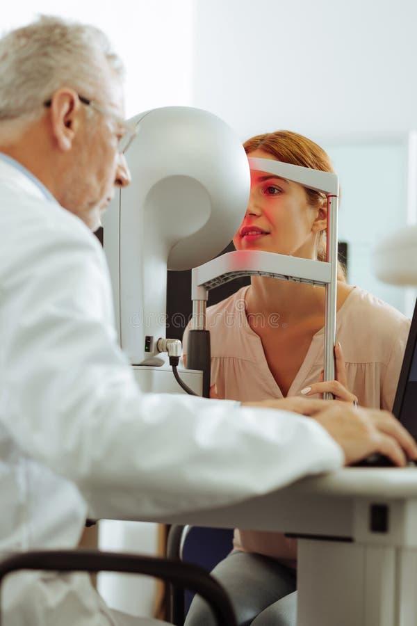 Ögonspecialist som använder modern teknologi för ögonundersökning royaltyfria bilder