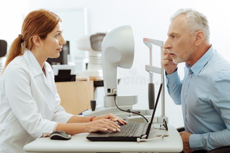 Ögonspecialist som ler, medan undersöka den åldriga grå färg-haired mannen arkivfoton
