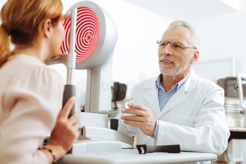 Ögonterapeut i exponeringsglas som ler, medan tala till patienten arkivfoto