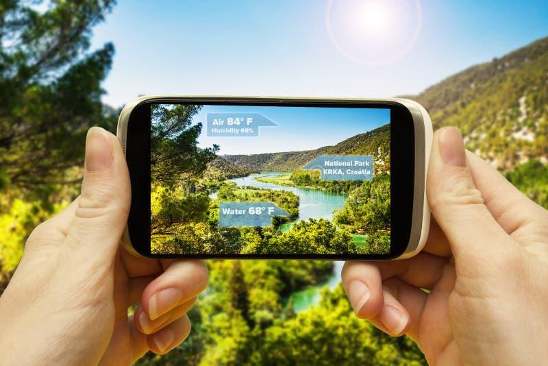 Ökade verklighetapplikationer för lopp och fritid Hand med en smartphoneapp A/R på-skärm information om stället av royaltyfria bilder