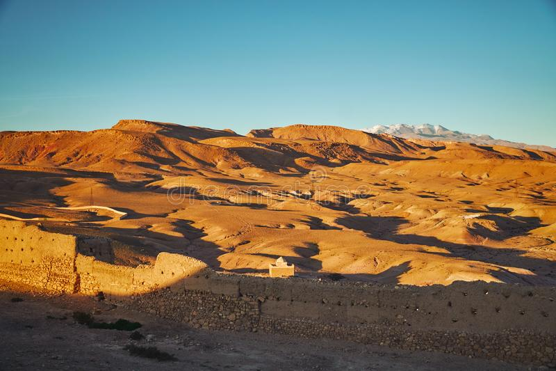 Öken nära Ait Ben Haddou ksar som tänds av aftonsolen arkivbilder