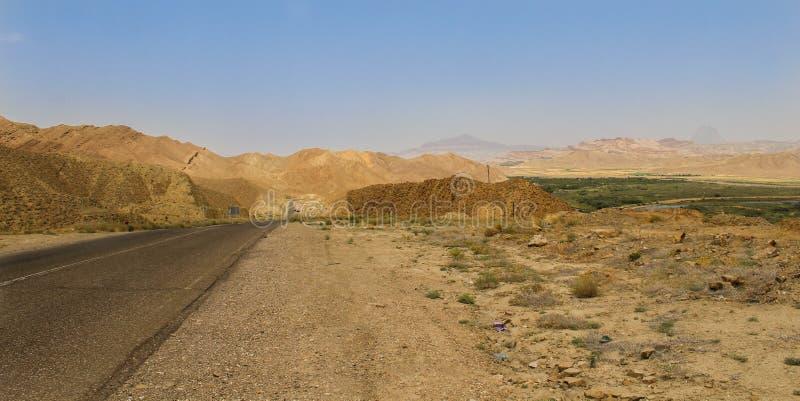 _öken väg av norr Iran med gräs, berg och en blå himmel royaltyfri foto