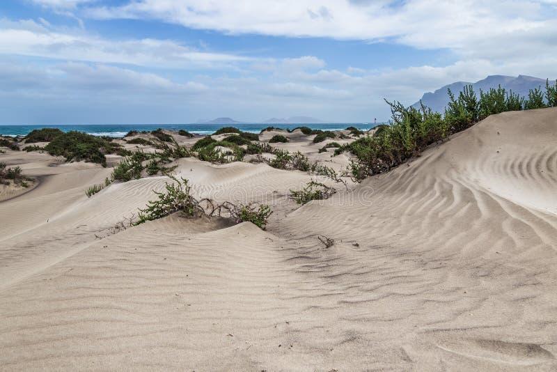 Ökenlandskap, med havet och bergen i bakgrunden i Lanzarote, kanariefågelöar arkivfoto