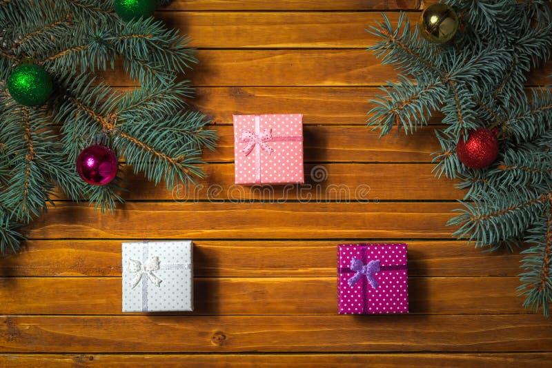 Ökologische, hölzerne Weihnachtsdekorationen Feiertagszusammensetzung mit Tannenzweigen, Spielzeugbälle, Geschenk boxies stockfoto