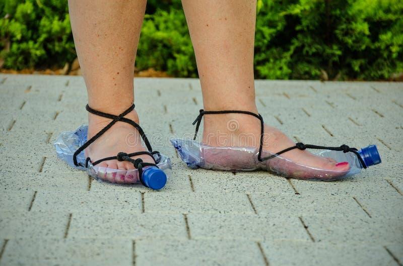 Ökonomische Frau, die Plastikflaschensandalen trägt lizenzfreies stockfoto