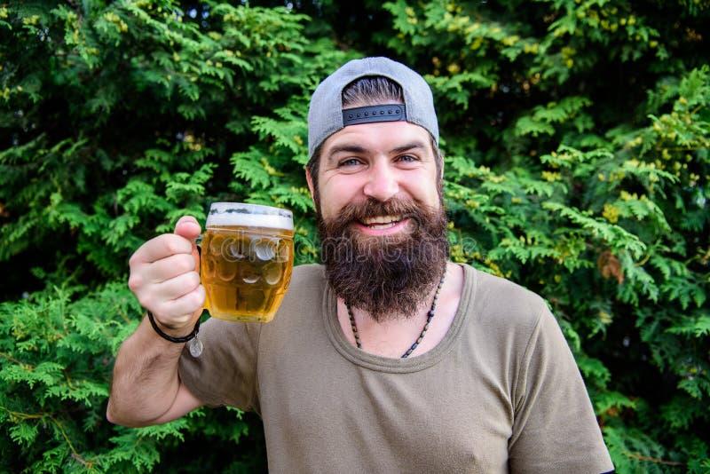 Öl är utmärkt sommardrinken Den skäggiga mannen som rymmer öl, rånar på sommarnaturen Brutal hipster som dricker på förnyande öl arkivfoto