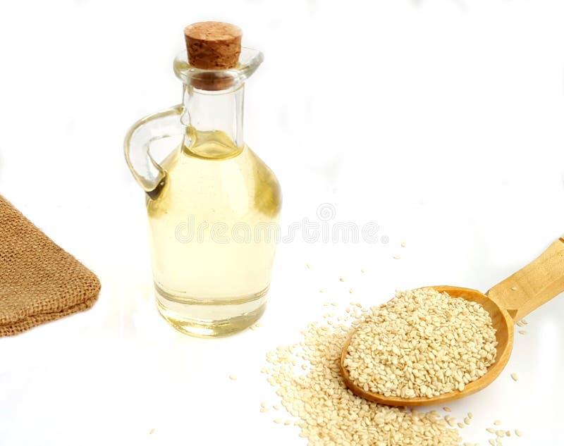 Öl des indischen Sesams in einer Glasflasche und in den Samen des indischen Sesams auf hölzernem Löffel stockfotografie