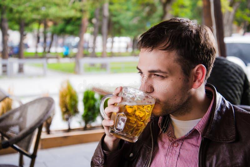 öl dricker mannen Sidosikt av den stiliga unga grabben som dricker den halv literen för lager, medan sitta på stångräknaren royaltyfri bild