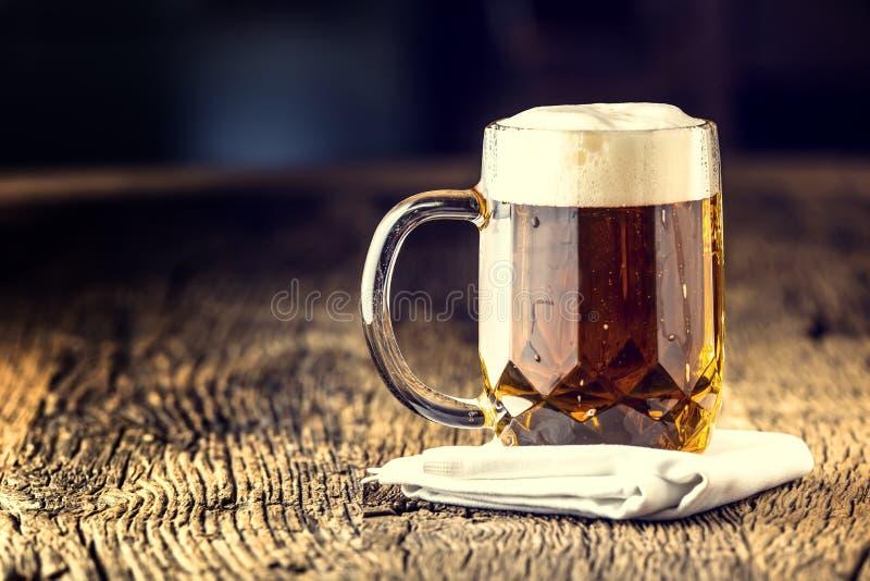 Öl Guld- öl för utkast i den glass kruset Utkastöl med fradga överst Kallt öl på mycket gammalt ekbräde arkivfoton