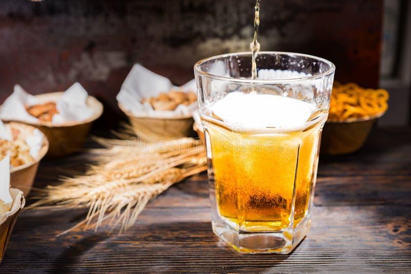 Öl häller in i glass near plattor med pistascher som är små royaltyfria foton