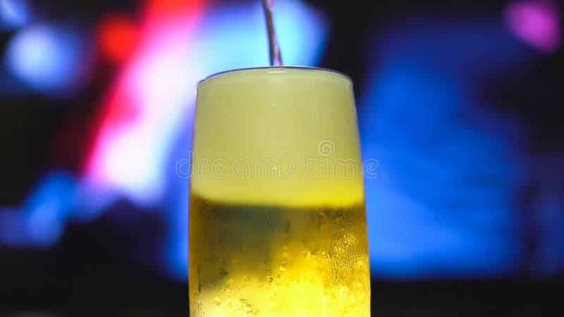 Öl häller uppifrån in i ett halv literexponeringsglas royaltyfri bild