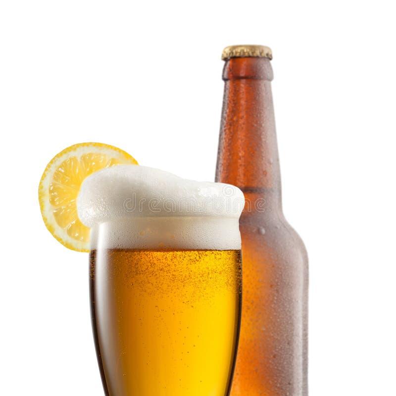 Öl i exponeringsglas med den isolerade citronen och flaskan royaltyfri bild
