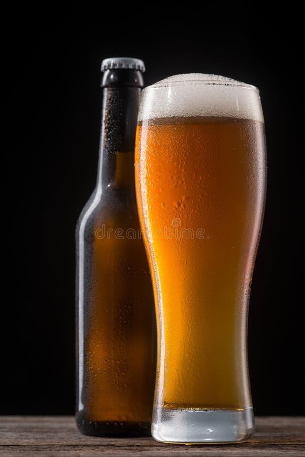 Öl i exponeringsglas och flaska arkivfoto