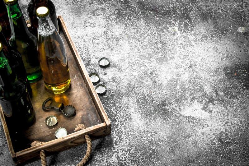 Öl i flaskor på ett trämagasin royaltyfri bild
