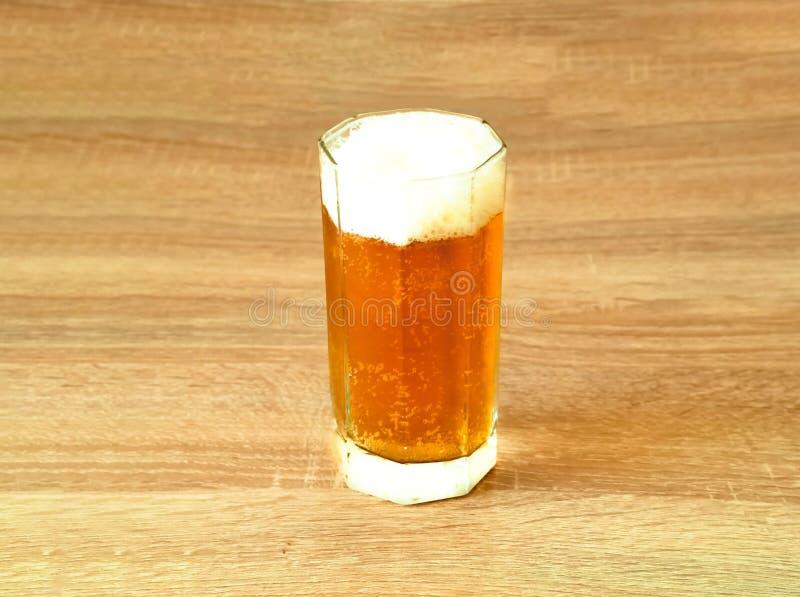 Öl med skum i exponeringsglasdryckeskärl på träbakgrund royaltyfri fotografi