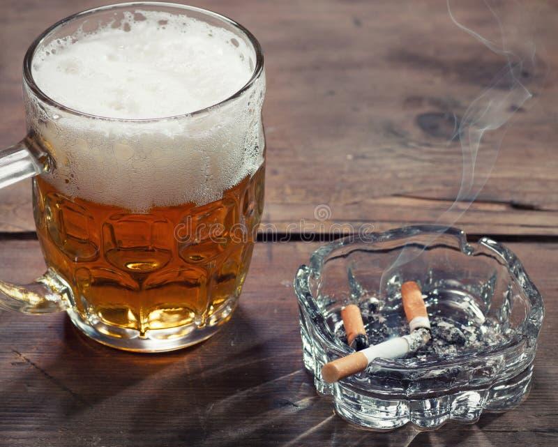 Öl och cigarett royaltyfria bilder