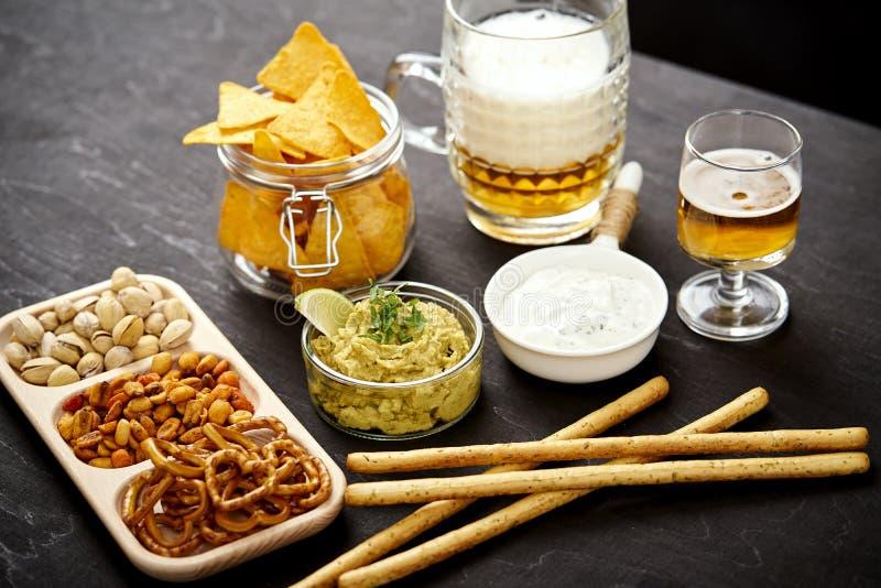 Öl och en bunke av guacamole med nachos och salta mellanmål på en gammal svart trätabell royaltyfri foto