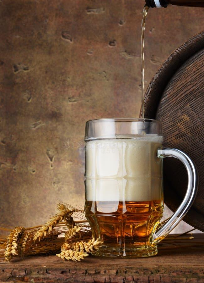 Öl rånar med veteöron, och trätrumman på en mörk väggbakgrund, häller öl arkivfoto