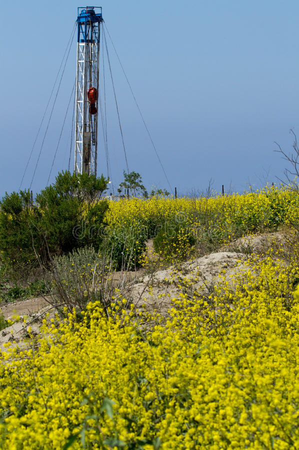 Öl Rig With Yellow Flower Foreground lizenzfreie stockfotografie