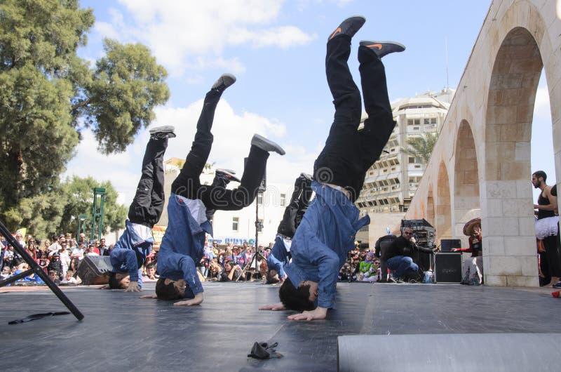 Öl-Sheva ISRAEL - mars 5, 2015: Grabbar är på meningarna av tonåringar som dansar på etappen - Purim royaltyfria bilder