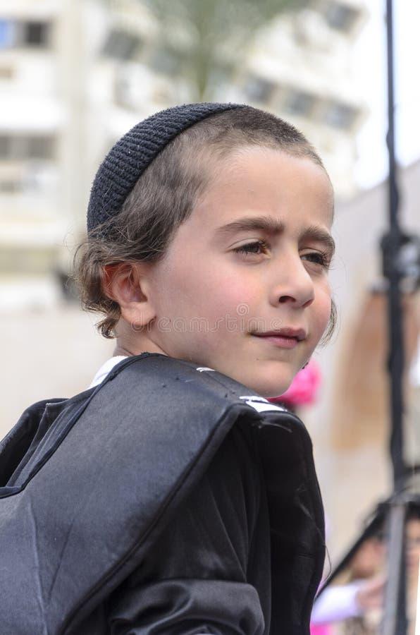 Öl-Sheva ISRAEL - mars 5, 2015: Ståenden av en tonårs- judisk pojke i svart och svart traver - Purim arkivbild