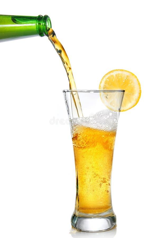 Öl som häller från flaskan in i exponeringsglas royaltyfri foto