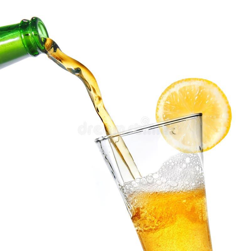 Öl som häller från flaskan in i exponeringsglas med citronen royaltyfri fotografi
