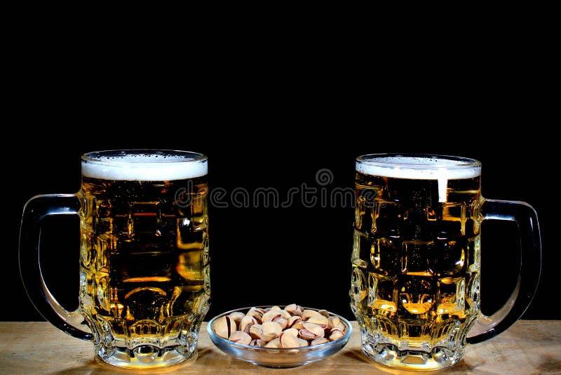 Öl två rånar och pistascher mot svart bakgrund arkivfoton